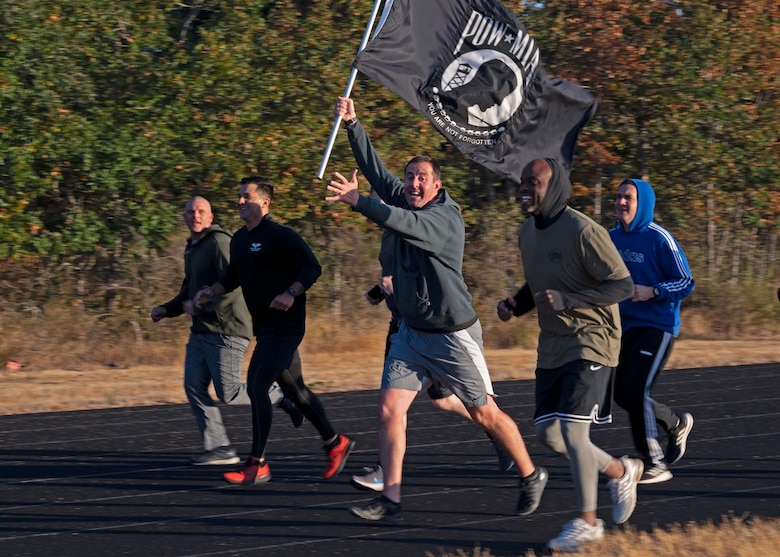 U.S. Air Force Maj. Zachary Magnin, 62nd Aircraft Maintenance Squadron commander, bears the POW/MIA flag as he and other 62nd AMXS leadership participate in the 24-hour POW/MIA Remembrance Run at Joint Base Lewis-McChord, Washington, Sept. 16, 2021. The official U.S. POW/MIA flag was created through the efforts of family members of POW/MIA Americans to display a suitable symbol that made the public aware of their loved ones who were being held prisoner or declared missing during the Vietnam War. (U.S. Air Force photo by Senior Airman Zoe Thacker)