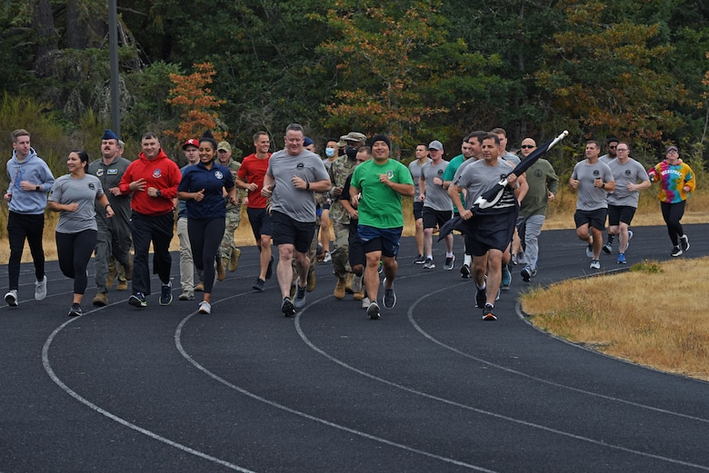 U.S. Airmen with the 62nd Airlift Wing participate in a 24-hour POW/MIA Remembrance Run on the McChord Field track at Joint Base Lewis-McChord, Washington, Sept. 15. 2021. The flag which they carried, the official U.S. POW/MIA flag, was created through the efforts of family members of POW/MIA Americans to display a suitable symbol that made the public aware of their loved ones who were being held prisoner or declared missing during the Vietnam War. (U.S. Air Force photo by Senior Airman Zoe Thacker)