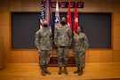 three people wearing army uniforms pose for a photo.