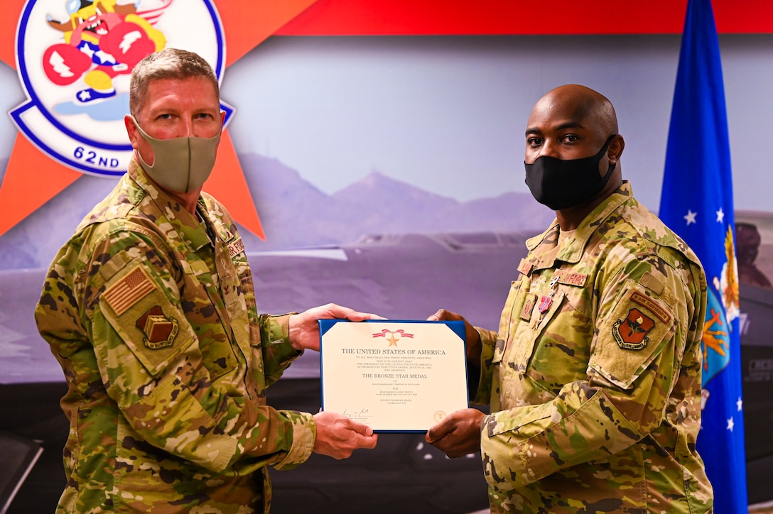 U.S. Air Force Col. William Ray, 56th Maintenance Group commander, awards the Bronze Star Medal to U.S. Air Force Master Sgt. Thomas Williams, 62nd Aircraft Maintenance Unit weapons loading non-commissioned officer in charge, for meritorious achievement in a deployed location Sept. 1, 2021, at Luke Air Force Base, Arizona.