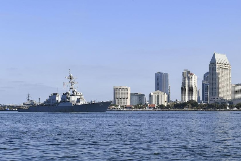 A military ship steams on the water with the buildings of a city behind it.