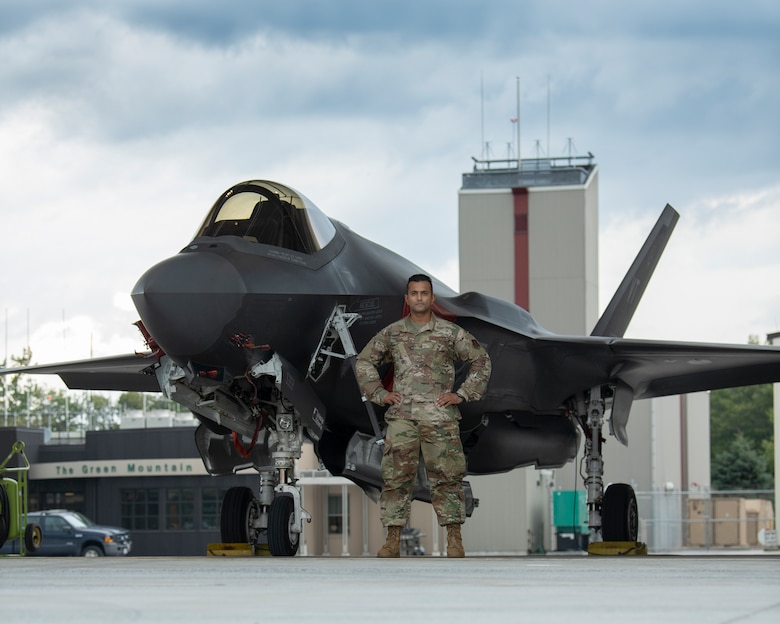 Picture of Airmen 1st Class Komalpreet Saini standing for a picture in front of an F-35A Lightning II aircraft assigned to the Vermont Air National Guard.