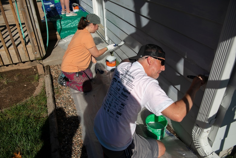 Michelle Butler (top), contract specialist,U.S. Army Corps of Engineers, Omaha District, Environmental Remediation Division, and Adam Ashton, special projects project manager, USACE Omaha District, paint the side of the house during the 2021 Paint-A-Thon, Aug. 21, 2021,