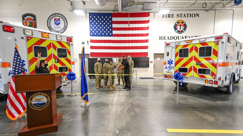 Base officials are flanked by two ambulances as they cut a ribbon.