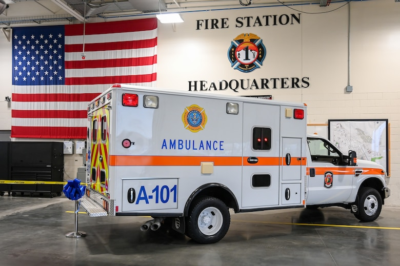 An ambulance inside the bay of the fire station with the American flag and fire station headquarters emblem on the wall behind it.