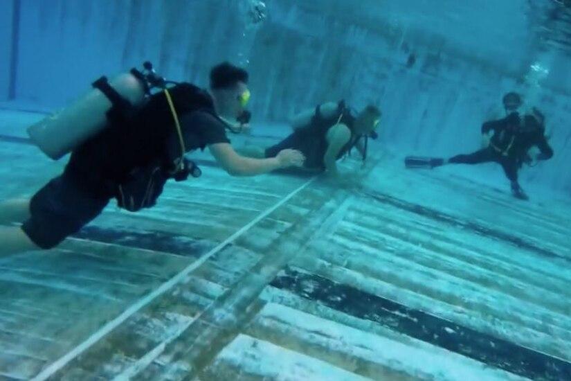 Three people scuba dive in a pool.