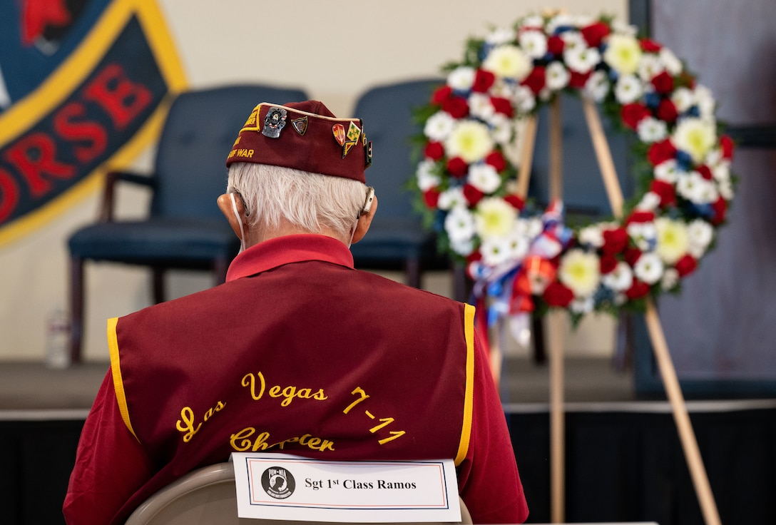 ex-POW sits in front of wreath