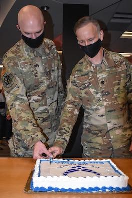 Service members cut cake for AF birthday celebration.