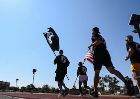People in fitness attire run with the POW/MIA and U.S. flag on a  sunny day