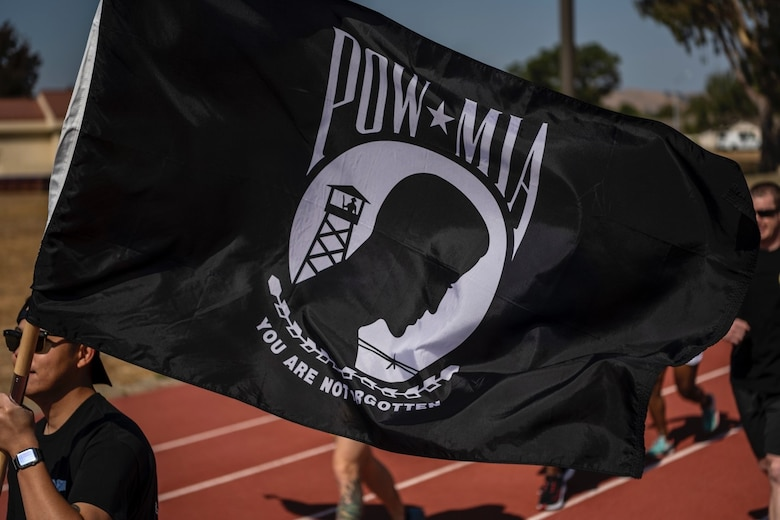 A man in a black shirt carries the POW/MIA flag while running on a sunny day