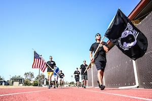 People in fitness attire run with the U.S. and POW/MIA flags on a sunny day