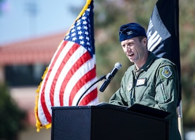 A uniformed Airman speaks into a microphone in front of the U.S. and POW/MIA flags