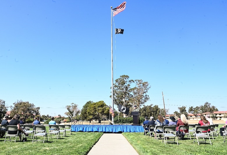 A stage is at the center of a congregation of attendees with a flag pole featured prominently on a sunny day