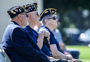 Representatives from VFW posts look to a stage on a sunny day