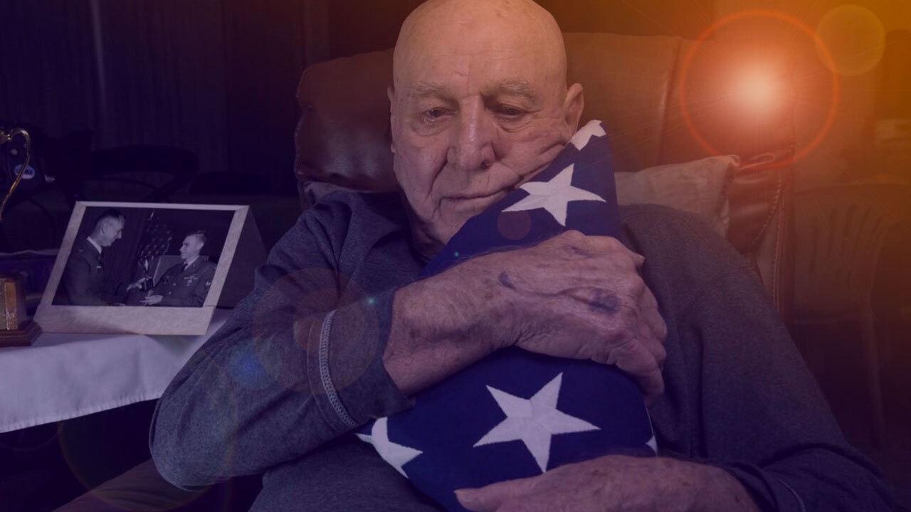 A seated man clutches a folded American flag to his chest.