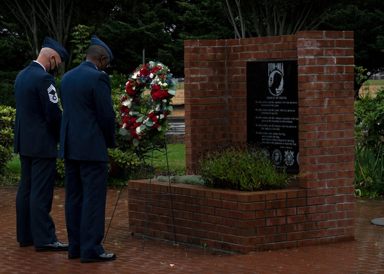 (From left) U.S. Air Force Chief Master Sgt. Christopher Clark, 627th Air Base Group superintendent, and Col. Christopher Hall, 627th ABG commander, observe a moment of silence after placing a wreath at the POW/MIA Memorial at Joint Base Lewis-McChord, Washington, Sept. 17, 2021. Team McChord Airmen gathered at the McChord War Memorial for the wreath ceremony to pay their respects to the more than 81,000 American heroes who were, and may still be, missing in action and those who were prisoners of war. (U.S. Air Force photo by Senior Airman Zoe Thacker)