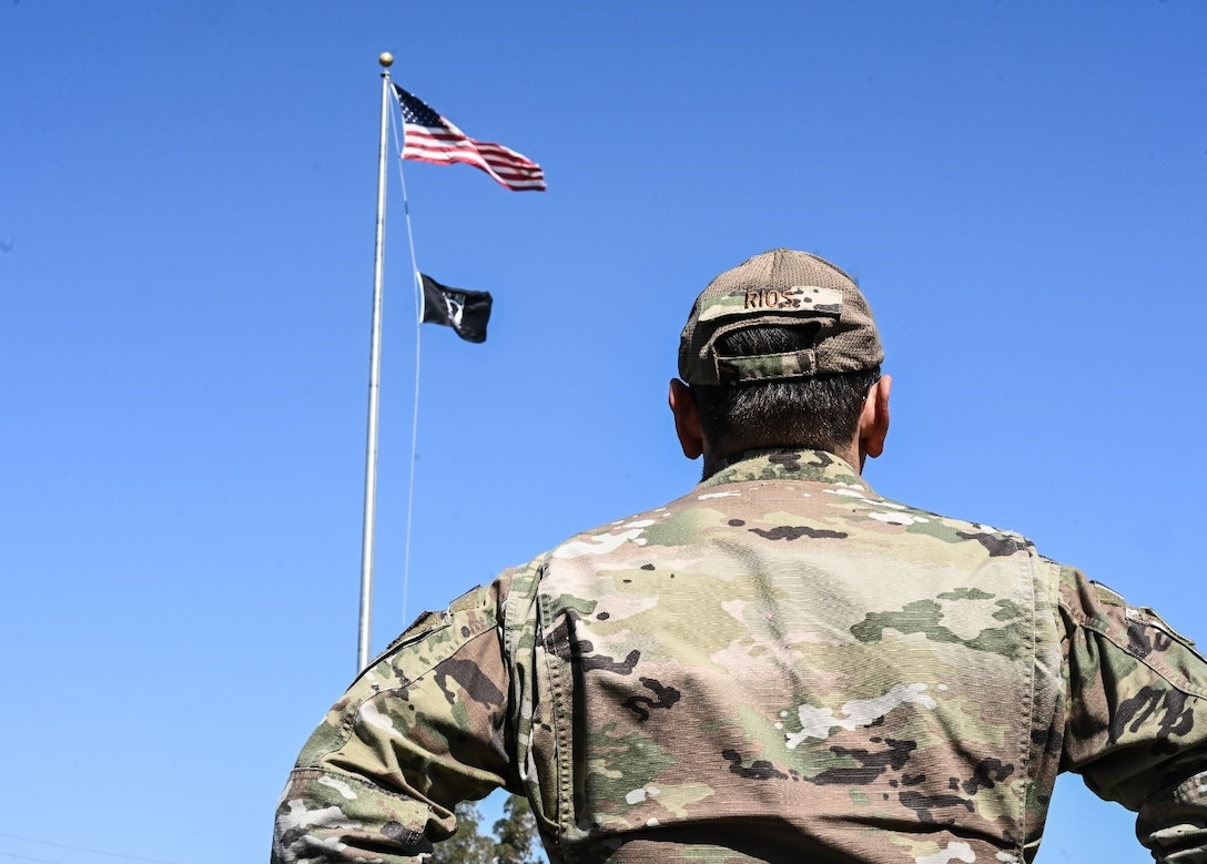 A uniformed Airman looks up at a flag pole bearing the U.S. and POW/MIA flags