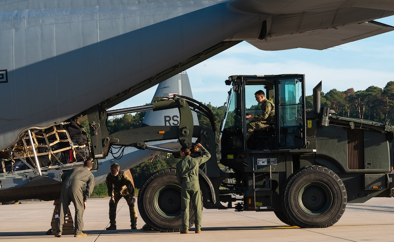Airmen load cargo on aircraft.