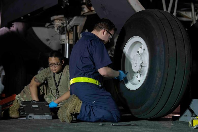 Senior Airmen Joseph Devera-Cruz, left, and Joshua James, right, 730th Air Mobility Squadron aircraft maintenance journeymen, prepare to change a tire on a C-5M Super Galaxy at Yokota Air Base, Japan, Sept. 13, 2021.