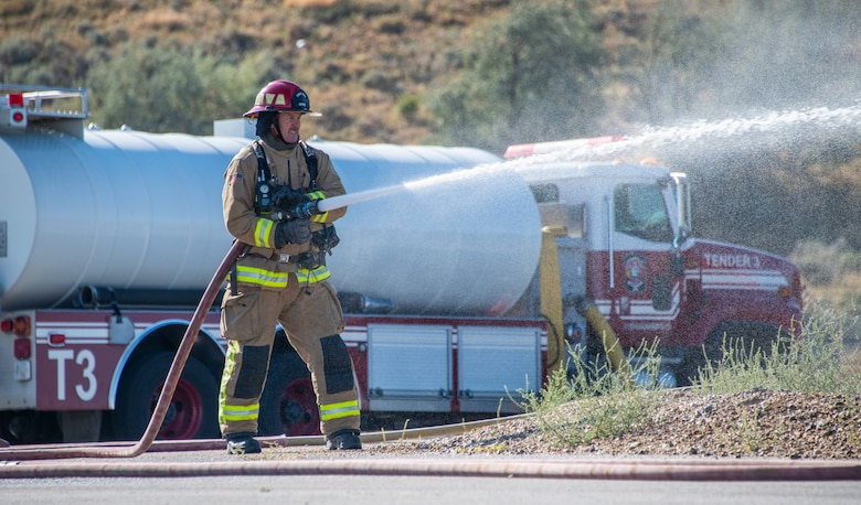 """U.S. Air Force Tech. Sgt. Wyatt Matthews, firefighter in the 419th Civil Engineer Squadron, extinguishes a fire onboard a """"downed aircraft"""" during a readiness training exercise"""