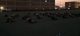 36 people lay on the ground with bent legs on a green turf field in the early morning.