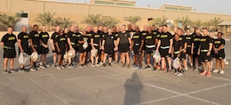 35 men and women stand in black shorts and shirts with yellow writing. Some hold plastic trashbags.