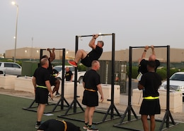 three Soldiers in black shorts and t-shirt observe three soldiers in black shorts and t-shirt on a pull up bar tucking their legs to their elbows.