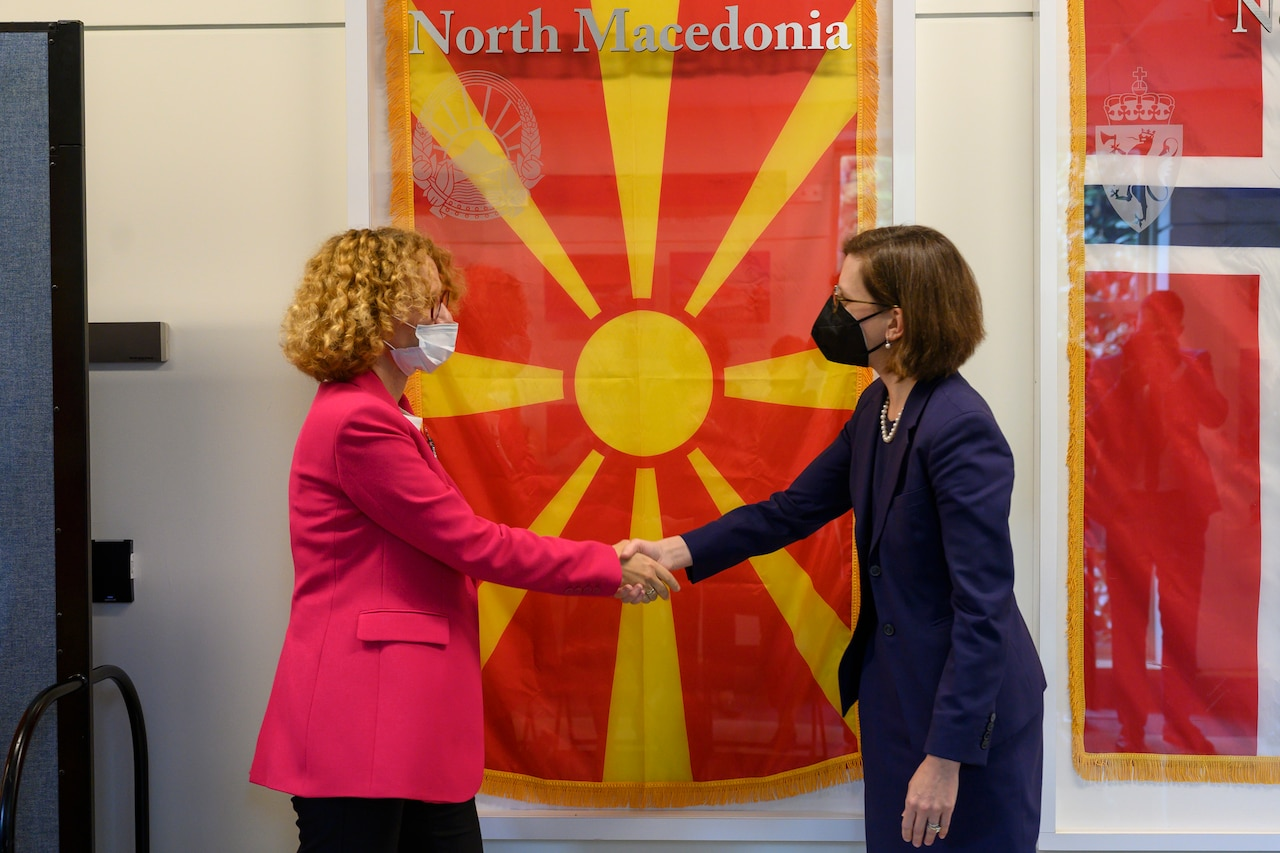 Two women shake hands in front of a yellow and red flag.