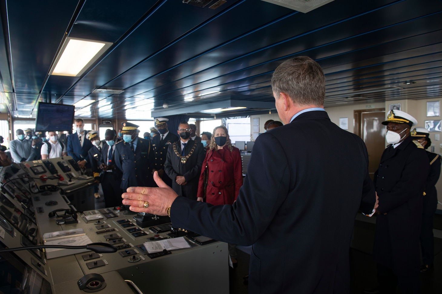 """Military Sealift Command Ship Master Joseph Darlak, right, addresses Jessica Long, chargé d'affaires, U.S. embassy in Namibia, second from right, His Worship Trevino Forbes, Mayor of Walvis Bay, third from right, Namibian Navy Rear Adm. Alweendo Paulus Amungulu, fourth from right, and a group of Namibian Navy leadership and U.S. embassy personnel during a tour of the Expeditionary Sea Base USS Hershel """"Woody"""" Williams (ESB 4), Sept. 17, 2021."""
