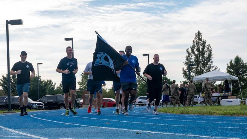 Service members run with the POW/MIA flag.