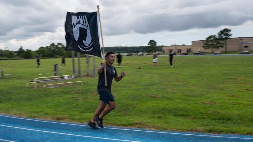 A service member runs with the POW/MIA flag during the 2021 POW/MIA walk/run