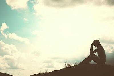 Silhouette of a person sitting on the group holding their head in their hands. Backdrop is of the blue sky.