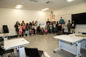 Brig. Gen. Matthew Higer, 412th Test Wing Commander, poses for a photo with teacher Julie Muniz's 5th grade class at Irving L. Branch Elementary School at the kick-off of the Math Tutoring Club on Edwards Air Force Base, California, Sept. 13. (Air Force photo by Katherine Franco)