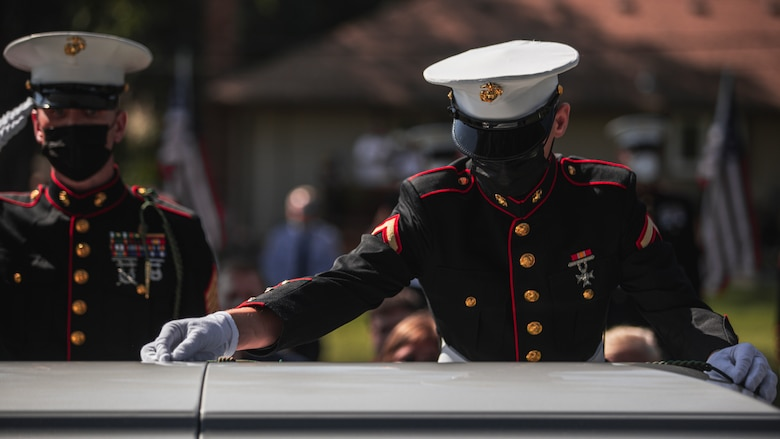 """U.S. Marine Corps Pfc. Evan Luisi, a native Palmerton, Pa., and a rifleman with 1st Battalion, 6th Marine Regiment (1/6), 2d Marine Division, lays his French Fourragere on the casket of Pfc. Glenn White, in Emporia, Kan., Sept. 18, 2021. White was in 1/6 when he was killed in action in Tarawa Atoll, Gilbert Islands, during World War II. """"Being able to participate in the ceremony was an amazing opportunity; laying down my French Fourragere was a huge honor,"""" Luisi said. """"My French Fourragere will be buried with him, to symbolize our brotherhood through 1/6. Something that I once wore will always be a part of his memory—that's incredible, I'll always remember that moment."""""""