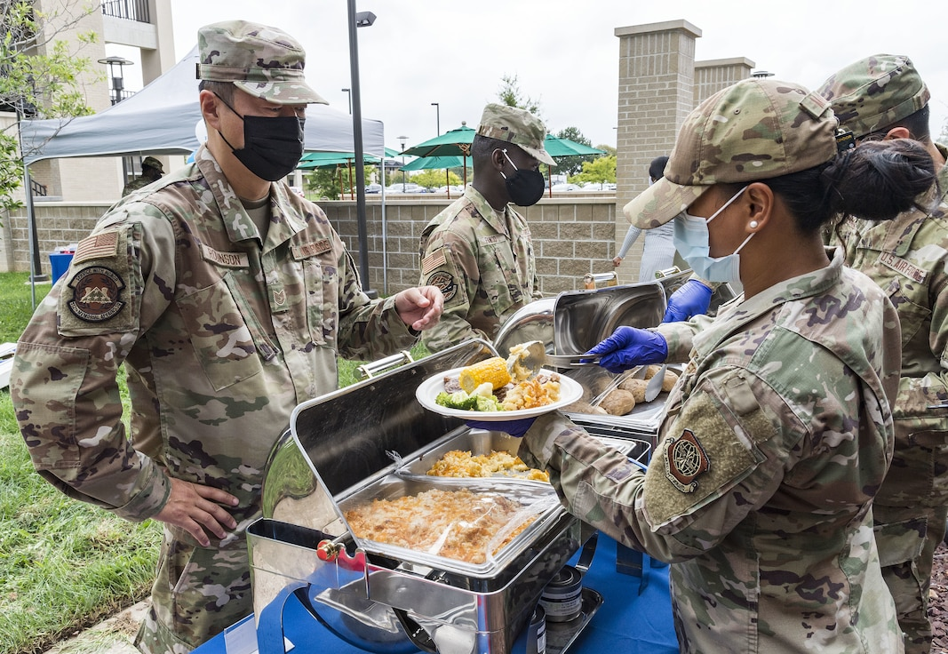 Staff Sgt. Miriam Malapit, right, 436th Force Support Squadron storeroom manager, serves food to Tech. Sgt. Kyle Robinson, left, 512th Mortuary Affairs Squadron mortuary technician at the Patterson Dining Facility on Dover Air Force Base, Delaware, Sept. 17, 2021. The DFAC held a picnic-style lunch commemorating the grand reopening, as well as a cake cutting celebrating the Air Force's 74th birthday. (U.S. Air Force photo by Roland Balik)