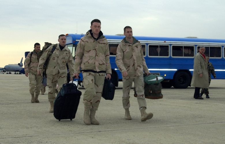US Air Force (USAF) Airmen from the 621st Air Mobility Operations Group (AMOG), McGuire Air Force Base (AFB), New Jersey (NJ), move from their bus toward an aircraft enroute to a CENTCOM (US Central Command) Area of Responsibility (AOR).