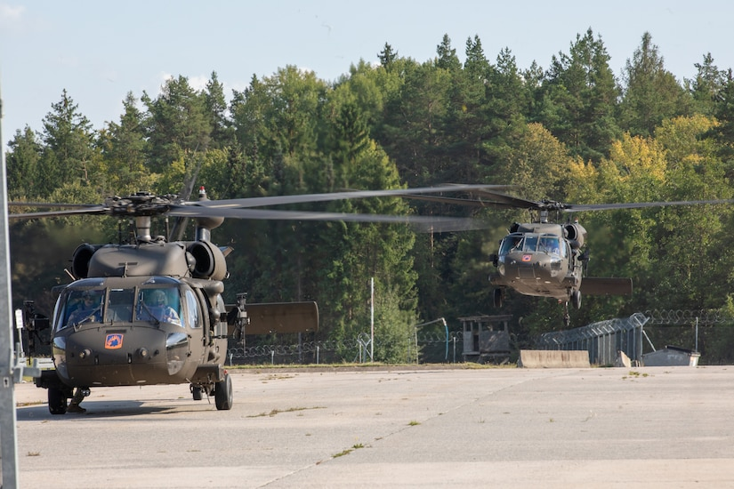 An helicopter takes flight next to a parked helicopter.