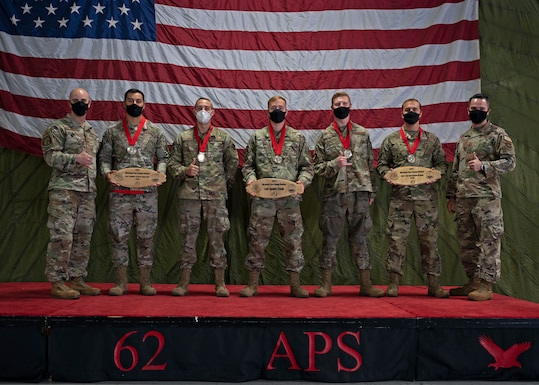 The Eagle Port Rodeo team with the 62nd Aerial Port Squadron receive their awards for winning two events and the title of Top Port Dawg Team at the 2021 Pacific Air Forces (PACAF) Port Dawg Rodeo at Joint Base Lewis-McChord, Washington, Sept. 15, 2021. The team traveled to Joint Base Pearl Harbor-Hickam, Hawaii, for the competition, which included everyday tasks of an aerial port Airman and used to showcase skill and build esprit de corps amongst Port Dawgs. (U.S. Air Force photo by Senior Airman Zoe Thacker)