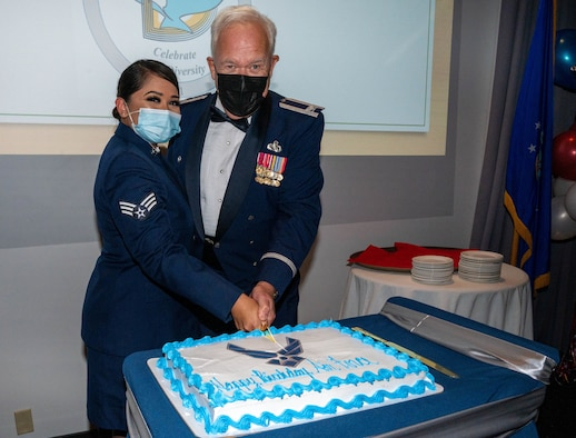 Senior Airman Chanelle Cabanayan, 436th Aerial Port Squadron administrative journeyman and retired Col. James Weber cut the Air Force's 74th birthday cake at Dover Air Force Base, Delaware, Sept. 18, 2021. Traditionally, the youngest and oldest Airmen at the Air Force Ball cut the cake to celebrate the Air Force birthday. (U.S. Air Force photo by Senior Airman Faith Schaefer)