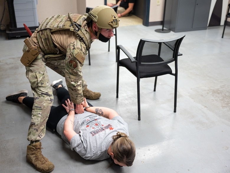 Senior Airman Zachary Burris, 2nd Security Forces Squadron installation patrolman, restrains a hostile actor during an active shooter exercise at Barksdale Air Force Base, Louisiana, Sept. 16, 2021. The exercise was designed to evaluate the training, readiness and capability of Barksdale's first responders in order to effectively respond to active shooter threats to the installation. (U.S. Air Force photo by Airman 1st Class Jonathan E. Ramos)