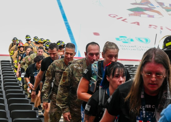 Brig. Gen. Gregory Kreuder, 56th Fighter Wing commander (left in Operational Camouflage Pattern uniform), and Chief Master Sgt. Daniel Weimer (right in OCP uniform), 56th Fighter Wing command chief, climb steps in the 9/11 Tower Challenge at Gila River Arena Sept. 7, 2021, in Glendale, Arizona.