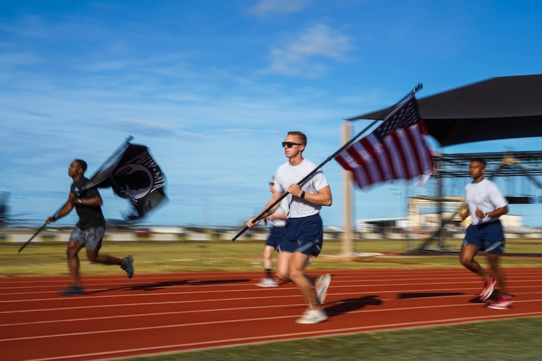 Airmen from 674th Airbase Group participate in a 24-hour run in honor of Prisoners of War and Missing in Action Remembrance Week at Joint Base Pearl Harbor-Hickam, Hawaii, Sept. 16, 2021. During the run, the POW/MIA flag will stay in motion for 24 hours by volunteers running with the flag to commemorate and symbolize the unwavering pursuit to recover all service members past and present. (U.S. Air Force photo by Airman 1st Class Makensie Cooper)