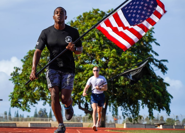 Airman 1st Class Jordan Nettles, 647th Civil Engineer Squadron water and fuels maintenance craftsman, participates in a 24-hour run in honor of Prisoners of War and Missing in Action remembrance week at Joint Base Pearl Harbor-Hickam, Hawaii, Sept. 16, 2021. During the run, the POW/MIA flag will stay in motion for 24 hours by volunteers running with the flag to commemorate and symbolize the unwavering pursuit to recover all service members past and present. (U.S. Air Force photo by Airman 1st Class Makensie Cooper)