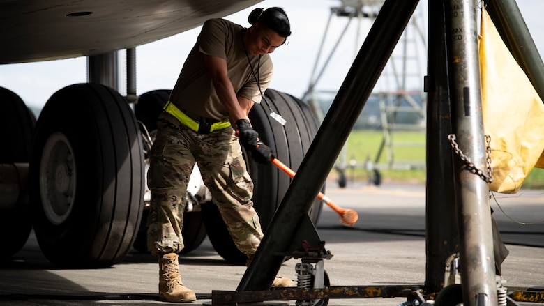 An Airman with a long hammer pounds into place a large airplane jack