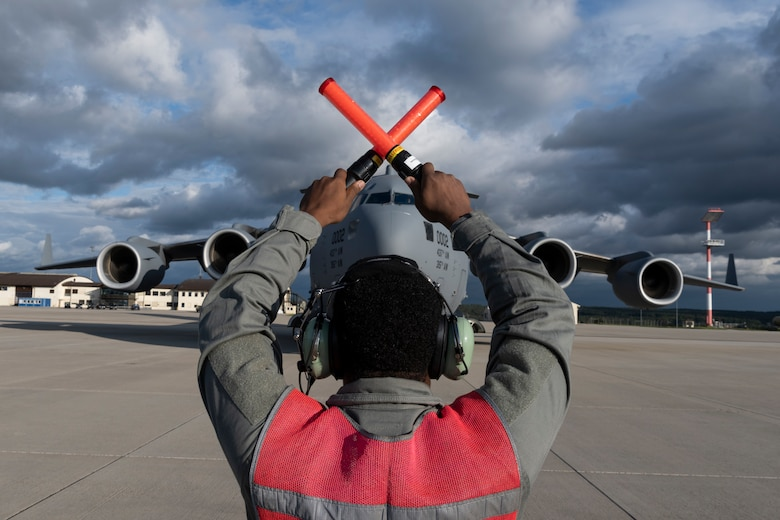 U.S. Air Force Senior Airman Leonard Bond, 726th Air Mobility Squadron aircraft electrical and environmental technician, marshals a U.S. Air Force C-17 Globemaster III cargo aircraft assigned to Joint Base Charleston, South Carolina, after it landed on Spangdahlem Air Base, Germany, Aug. 27, 2021.