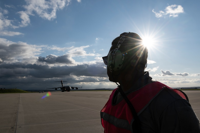 U.S. Air Force Senior Airman Leonard Bond, 726th Air Mobility Squadron aircraft electrical and environmental technician, waits to marshal a U.S. Air Force C-17 Globemaster III cargo aircraft assigned to Joint Base Charleston, South Carolina, after it landed on Spangdahlem Air Base, Germany, Aug. 27, 2021.