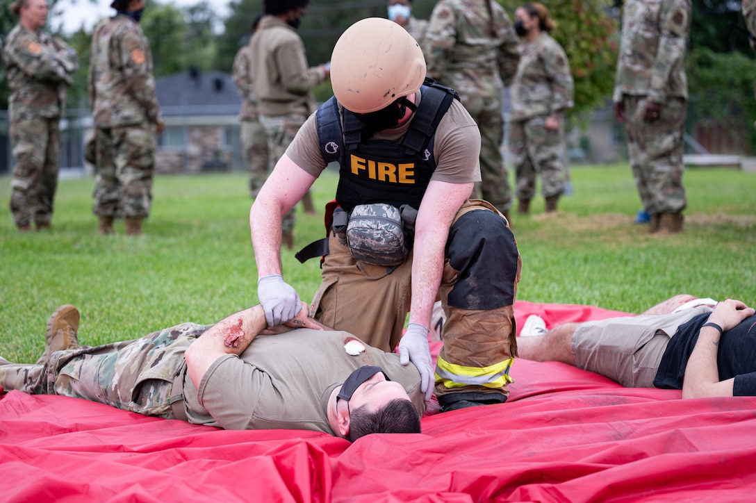 Airman 1st Class Christian Moneypenny, 2nd Civil Engineer Squadron firefighter, provides medical care to an injured actor during an active shooter exercise at Barksdale Air Force Base, Louisiana, Sept. 16, 2021. Firefighters are responsible for both firefighting and emergency medical response as first responders. (U.S. Air Force photo by Airman 1st Class Jonathan E. Ramos)