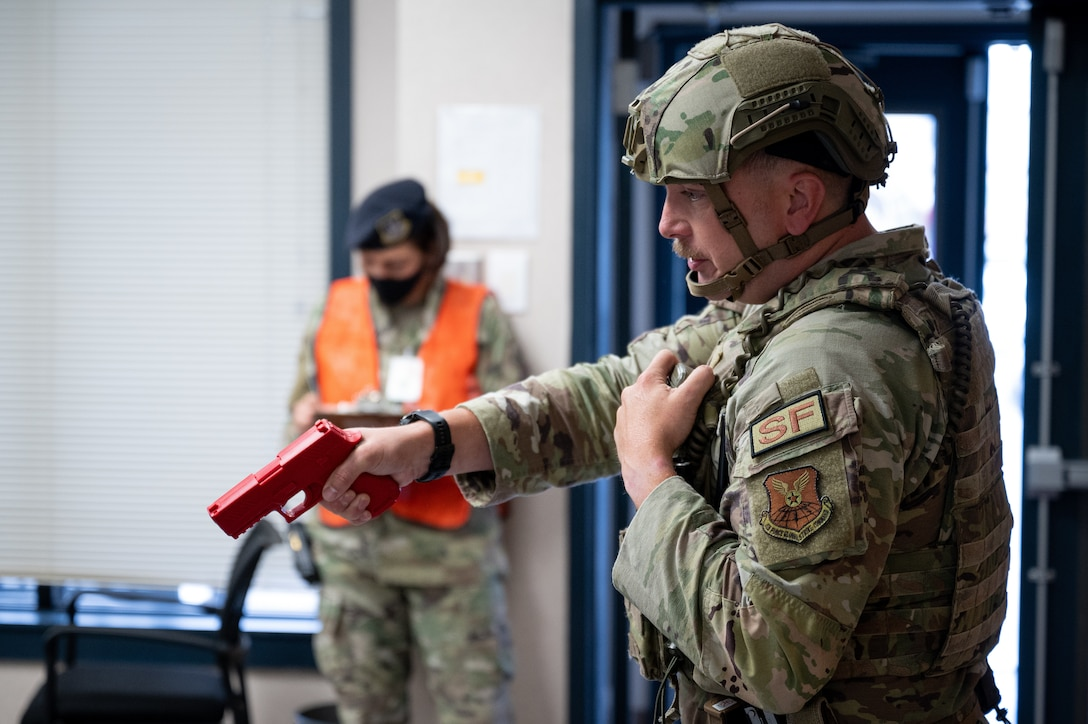 Tech. Sgt. Jacob Udell, 2nd Security Forces Squadron flight sergeant, draws a weapon on a hostile during an active shooter exercise at Barksdale Air Force Base, Louisiana, Sept. 16, 2021. The exercise was designed to evaluate the training, readiness and capability of Barksdale's first responders in order to effectively respond to active shooter threats to the installation. (U.S. Air Force photo by Airman 1st Class Jonathan E. Ramos)