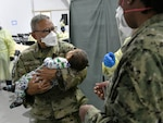 Washington Air National Guard Master Sgt. Andy Remis, assigned to the 116th Air Support Operations Squadron, Camp Murray, Wash., lends a helping hand, holding an Afghan child at the Task Force Liberty Village medical station, Joint Base McGuire-Dix-Lakehurst, New Jersey, Sept. 11, 2021. The Department of Defense, through U.S. Northern Command, and in support of the Department of Homeland Security, is providing transportation, temporary housing, medical screening, and general support for at least 50,000 Afghan evacuees at suitable facilities, in permanent or temporary structures, as quickly as possible. This initiative provides Afghan personnel essential support at secure locations outside Afghanistan. (National Guard photo by Master Sgt. John Hughel, Washington Air National Guard)