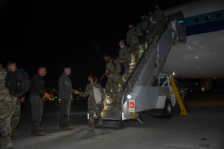 Airmen descend aircraft stairs to shake hands with the 5th Bomb Wing commander